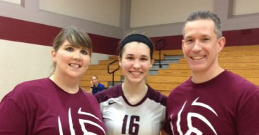 volleyball player stands with parents in empty gymnasium during recruiting journey
